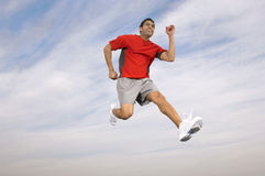 Athlete Running Midair. Low angle of a male athlete running midair against the sky and clouds stock images