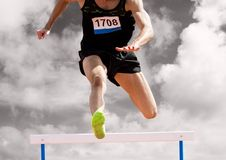 Athlete running over hurdle Royalty Free Stock Images