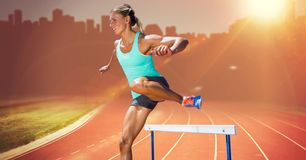 Athlete running over hurdle Stock Photos