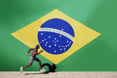 Athlete running past Brazilian flag stock photography