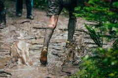 Athlete running through puddles of mud Stock Image