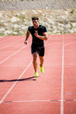 Athlete running on the racing track. Determined athlete running on the racing track on a sunny day Royalty Free Stock Photos