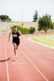 Athlete running on the racing track. On a sunny day Royalty Free Stock Images