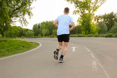 The athlete runs along the asphalt road. The guy in the white T-shirt in the summer Stock Image