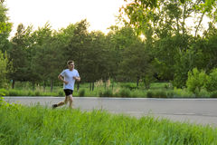 The athlete runs along the asphalt road. The guy in the white T-shirt in the summer Royalty Free Stock Photo