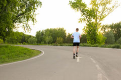 The athlete runs along the asphalt road. The guy in the white T-shirt in the summer Stock Photos