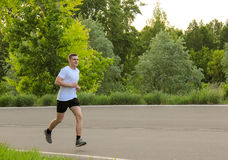 The athlete runs along the asphalt road. The guy in the white T-shirt in the summer Stock Photo