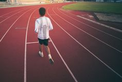 Athlete runs around the stadium. In the morning Royalty Free Stock Photography