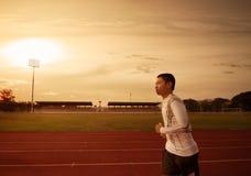 Athlete runs around the stadium. In the morning Royalty Free Stock Photos