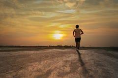 Athlete runs around the stadium. In the morning Stock Photo