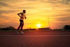 Athlete runs around the stadium. In the morning Stock Image