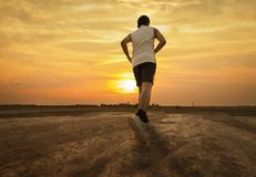 Athlete runs around the stadium. In the morning Stock Photos