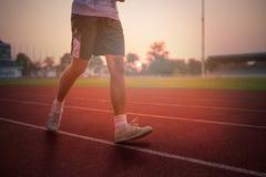 Athlete runs around the stadium in the morning. Athlete runs around the stadium with sunset or sunrise background Royalty Free Stock Image