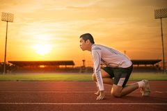 Athlete runs around the stadium in the morning. Athlete runs around the stadium with sunset or sunrise background Stock Images