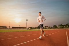 Athlete runs around the stadium in the morning. Athlete runs around the stadium with sunset or sunrise background Royalty Free Stock Images