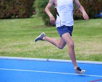 Athlete runs on athletics track during racing Royalty Free Stock Photography