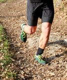 Athlete runs fast during the triathlon race. Athlete runs during the triathlon race on the mountain trail w royalty free stock photo