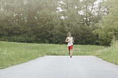 Athlete runs in the middle of the road Royalty Free Stock Photos