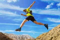 Athlete runs off-road. Jumps over a ravine. Trail runner in the desert. A man wearing a yellow T-shirt and shorts. National Park Altyn-Emel. Kazakhstan stock photography