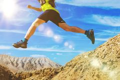 The athlete runs off-road. Jumps over a ravine. Trail runner in the desert. A man wearing a yellow T-shirt and shorts. National Park Altyn-Emel. Kazakhstan royalty free stock photos