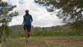 Athlete runs over rough terrain in mountains. Slow motion. Treil running. Off-road running stock footage