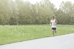 Athlete runs on the road Royalty Free Stock Photo