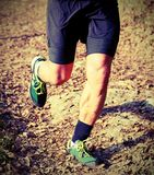 Athlete runs during the triathlon race with old toned effect. Athlete runs during the triathlon race on the mountain trail with old toned effect royalty free stock photo