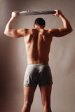 Athlete's back. Male model in briefs striking a pose with his shirt stretched over his head muscular back Royalty Free Stock Photography