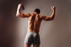 Athlete's back. Male model in briefs striking a pose with his shirt stretched over his head muscular back flexing Stock Photography