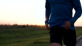 The athlete's body of a runner close-up while Jogging