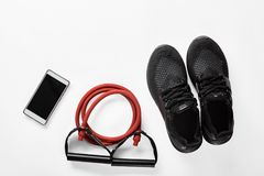 Athlete`s male set. With mobile phone, elastic expander and gymshoes Stock Image