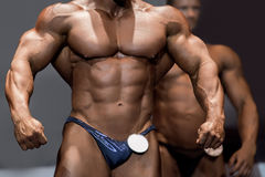 Athlete`s muscular torso and arms. Huge bodybuilder posing on stage. Sportsman in outstanding shape. Body trained to physical perfection Royalty Free Stock Photo