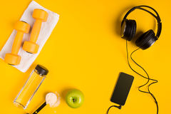 Athlete`s set with female clothing, dumbbells and bottle of water on yellow background Royalty Free Stock Image