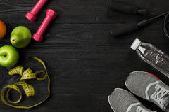 Athlete`s set with female clothing, sneakers and bottle of water on dark background Royalty Free Stock Photos