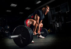 Athlete screams to motivate himself to perform an exercise calle. Athlete screams in the gym to motivate himself to perform an exercise called deadlift Royalty Free Stock Image