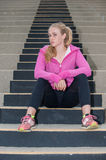 Athlete seated on the black steps. Attractive blond sitting on concrete steps with head turned to left stock image