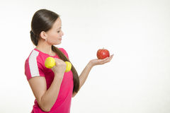 Athlete shakes muscles of the right hand dumbbell and looking at an apple in her left hand Royalty Free Stock Photography
