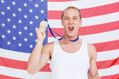 Athlete showing his gold medal in front of american flag Royalty Free Stock Image