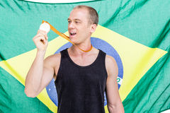 Athlete showing his gold medal in front of brazilian flag. Athlete posing with gold medal around his neck in front of brazilian flag Royalty Free Stock Photography