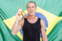 Athlete showing his gold medal in front of brazilian flag. Athlete posing with gold medal around his neck in front of brazilian flag Royalty Free Stock Images