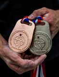 Athlete shows a bronze and a silver medals stock images