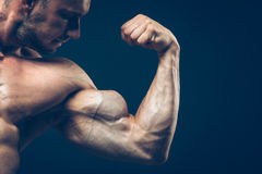 The athlete shows his beautiful body on black Royalty Free Stock Photography