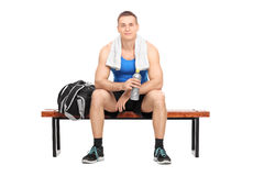 Athlete sitting on a bench holding a water bottle Royalty Free Stock Image
