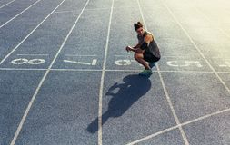 Sprinter sitting on running track. Athlete sitting on running track with a water bottle in hand. Runner sitting at the start line wearing earphones and mobile Stock Photos