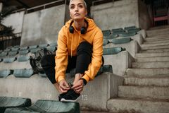 Athlete sitting in stands of a stadium tying shoelace. Female runner getting ready for workout. Woman sitting in the stands of a stadium tying shoe lace royalty free stock image