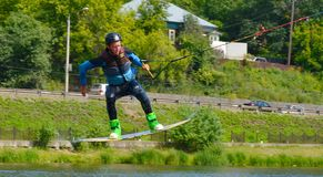 The athlete with snowboard hold on to the rope and the boat accelerates. Russia, Volgodonsk - June 18, 2015: Water snowboard. The athlete with snowboard hold on Royalty Free Stock Images