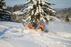 Athlete on a snowmobile moving in the mountains Stock Photo