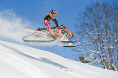 Athlete on a snowmobile moving  in the mountains. SAKHALIN RUSSIAN - JANUARY 23 : Oleg Bibikov moving snowmobile in winter forest in the mountains of Sakhalin Royalty Free Stock Photo