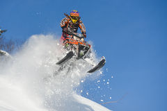 Athlete on a snowmobile moving  in the mountains. SAKHALIN RUSSIAN - JANUARY 23 : Oleg Bibikov moving snowmobile in winter forest in the mountains of Sakhalin Royalty Free Stock Photography