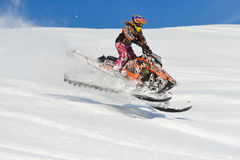 Athlete on a snowmobile moving  in the mountains. SAKHALIN RUSSIAN - JANUARY 23 : Oleg Bibikov moving snowmobile in winter forest in the mountains of Sakhalin Royalty Free Stock Photos